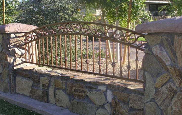 Сочетание опор из камня с кованым забором