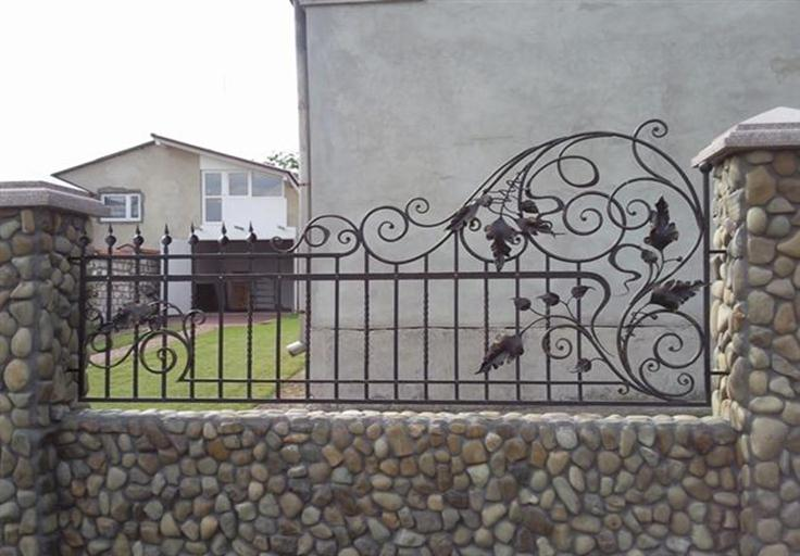 Комбинация опор из камня с кованым забором